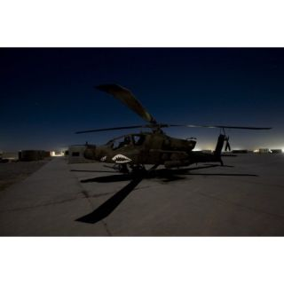 An AH 64D Apache Longbow Block III attack helicopter waits on the flight line at night at Camp Speicher Poster Print (17 x 11)